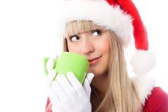 Dreamy girl having a cup of tea. Dreamy girl dressed as Santa having a cup of tea Royalty Free Stock Photos
