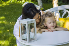 Dreamy girl with her mother. quarrel concept. Girl  and mother standing near table with decorative  box for wishes Royalty Free Stock Photo