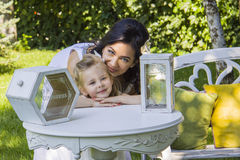 Dreamy girl with her mother. Girl  and mother standing near table with decorative  box for wishes Stock Photos