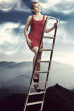 Dreamy girl on ladder Royalty Free Stock Images