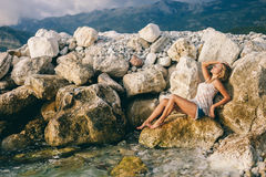 Dreamy girl lay on rock beach with mountains background Stock Photography