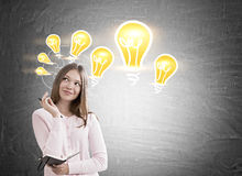 Dreamy girl and light bulbs on blackboard Royalty Free Stock Photography
