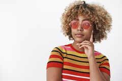 Dreamy girl looking away as thinking. Charming stylish african-american woman in trendy 90s outfit with cool red. Sunglasses gazing at upper left corner royalty free stock photography