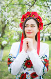 Dreamy girl in national clothes in a flowering garden Stock Image