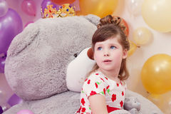 Dreamy girl posing on backdrop of teddy bear Royalty Free Stock Photo