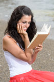 Dreamy girl reading book at beach Stock Photography