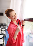 Dreamy girl in restaurant playfully looks out the window Royalty Free Stock Photos