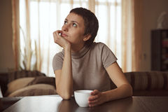 Dreamy girl sitting with a cup of coffee Royalty Free Stock Images