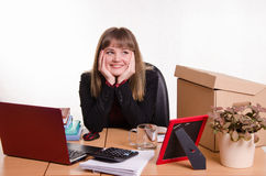 Dreamy girl sitting at office desk Royalty Free Stock Image