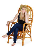 Dreamy girl is sitting in a wicker chair Royalty Free Stock Photos
