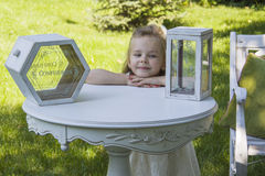 Dreamy girl. Girl standing near table with decorative box for wishes stock images