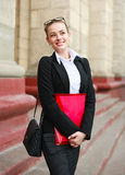 Dreamy girl student in business suit in front of university Royalty Free Stock Photography