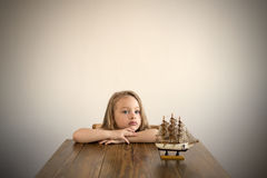 Dreamy girl at a table with a little boat. Dreamy 4-year-old girl sitting at a wooden table. A little boat standing on a table next to her. Natural light is used Stock Image