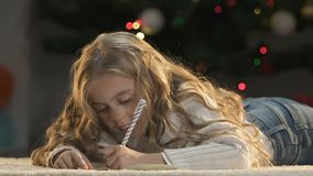 Dreamy girl writing latter to Santa asking for gift, faith in miracle, childhood. Stock footage stock video
