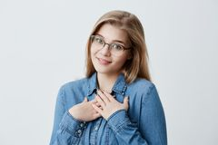 Dreamy glad female looks at camera with pleasure and gratitude, keeps hands together on chest, smiles happily, imagines. Pleasant moments in her life. Pleasant Stock Photography