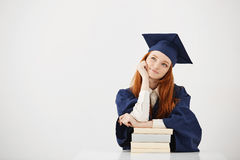 Dreamy graduate girl smiling thinking sitting with books. Copy space. Royalty Free Stock Photo