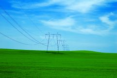 Dreamy grassy hill and powerlines. Powerlines in green field Royalty Free Stock Image