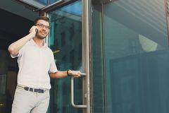 Dreamy handsome businessman leaving building and making a call Royalty Free Stock Image