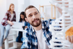 Dreamy handsome guy looking inspired by science. Inspired young scientist. Vibrant engaged clever men examining the model of human DNA while sitting in class and Royalty Free Stock Photo