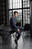 Pretty male model with dark brown hair in dark blue style. Dreamy handsome slim young guy sitting on a table with his head down royalty free stock photos