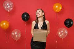 Dreamy happy girl in black dress celebrating looking up hold golden box with gift present on bright red background air