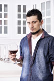 Dreamy happy well looking man drinking red wine in the kitchen Stock Photo