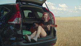 Dreamy hipster woman playing guitar in car trunk. Dreamy hipster woman playing acoustic guitar sitting in open car trunk during summer vacations road trip stock video footage