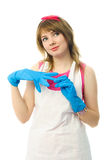 Dreamy housewife putting on rubber gloves Royalty Free Stock Photos