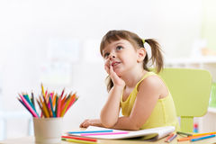Dreamy kid girl drawing with color pencils Royalty Free Stock Photo