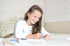 Dreamy kid girl drawing and paint with color pencils stock photos