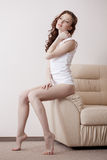 Dreamy leggy model posing on leather couch Royalty Free Stock Photos