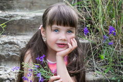 Dreamy little girl with a bouquet on the stairs Royalty Free Stock Photos