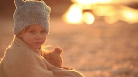 Dreamy little girl hugging a teddy bear and looking away while sitting on the seashore slow motion stock video