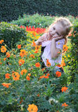 Dreamy little girl with long blonde hair sitting on poppy field Royalty Free Stock Photo
