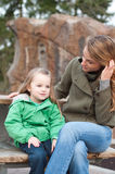 Dreamy little girl resting on a bench with mother Stock Image