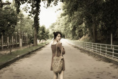 Dreamy look of asian beautiful lady stand in middle of road and. Look back with smile.soft tone Stock Image