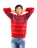 Dreamy look. Young man in red sweater smiles standing on white background Royalty Free Stock Photo