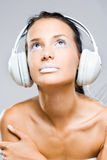 Dreamy looking young music listener. Stock Image
