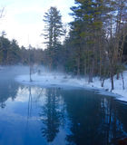 Dreamy, Misty, Magical Fairy World Meditation. Fog and snow on a deep blue river in Maine with very clear still water and a forest of evergreen trees reflected Stock Photos
