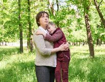 Dreamy mom and daughter in summer park, sunlight, green grass and trees. Dreamy mom and daughter in summer park, sunlight, green  grass and trees Royalty Free Stock Photos