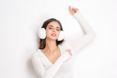 Dreamy music lover. Gorgeous dreamy young brunette woman wearing white headphones Royalty Free Stock Images