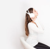 Dreamy music lover. Gorgeous dreamy young brunette woman wearing white headphones royalty free stock image