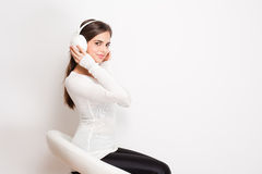 Dreamy music lover. Gorgeous dreamy young brunette woman wearing white headphones Stock Photos