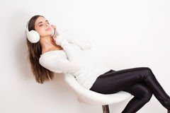 Dreamy music lover. Gorgeous dreamy young brunette woman wearing white headphones stock photography