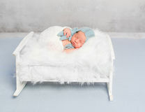 Dreamy newborn boy holding toy sleeps. On little bed covered with white fluffy blanket Royalty Free Stock Images