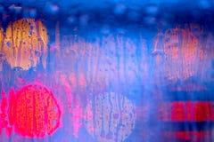 Dreamy night city lights behind rainy window. Blue colors Stock Photography