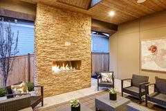 Dreamy outdoor covered patio with stone fireplace. A beadboard ceiling with skylight, rattan armchairs, sofa and ottomans overlooking the expansive backyard Stock Images