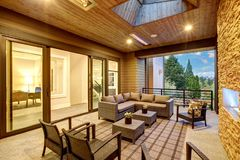 Dreamy outdoor covered patio with stone fireplace. A beadboard ceiling with skylight, rattan armchairs, sofa and ottomans overlooking the expansive backyard Royalty Free Stock Image