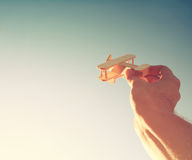 Dreamy photo of man's hand holding wooden toy airplane. Close up photo of man's hand holding wooden toy airplane against the sky. retro filtered image Royalty Free Stock Photos