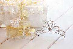 Dreamy photo of pearls necklace, tiara and perfume bottle royalty free stock image